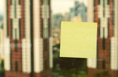 Yellow sticky paper  over blurred background Royalty Free Stock Image