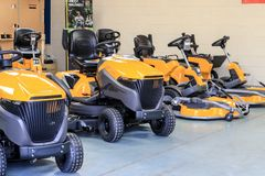 A row of sit on lawn mowers. Yellow stiga sit on lawn mowers for cutting lawn grass  Doing chores and home maintenance in show room Royalty Free Stock Photos