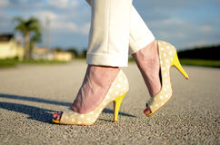 Yellow Stiletto shoes on woman's feet. Yellow heel shoes in summer sunshine of Florida royalty free stock photo