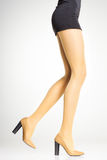 Yellow stockings on sexy woman legs  on grey. Background Royalty Free Stock Photography