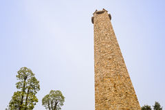 Yellow stone tower in sunny sky of spring afternoon Stock Photography