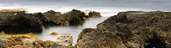 Yellow stones in the surf. Panorama stock photo