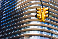 Yellow stop light in front of a large building Royalty Free Stock Image