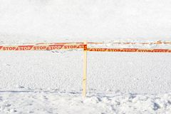 Yellow STOP tape surrounded frozen ice hole Royalty Free Stock Image