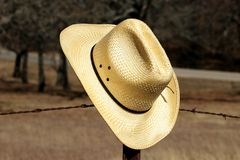 Yellow Straw Cowboy Hat on Fence. Close-up of a yellow straw cowboy hat as it hangs on the fence post of a rusty barbed wire fence with a fall countryside stock image