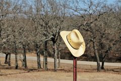 Yellow Straw Cowboy Hat Hanging of Rusty Fence Post. A yellow straw cowboy hat hangs on a rusty barbed wire fence post at the end of a day of hard work. Trees royalty free stock photos