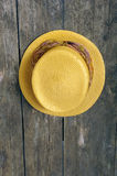 Yellow straw hat on an old weathered wall Royalty Free Stock Photography