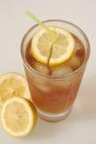 Yellow straw threw lemon. Glass of Iced Tea with a yellow straw going threw lemon royalty free stock photo