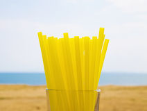 Yellow straws in a transparent glass on the beach Stock Image