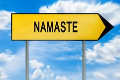 Yellow street concept namaste sign. Isolated on sky background close royalty free stock image
