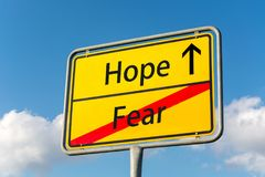 Yellow street sign with Hope ahead leaving Fear behind stock photo