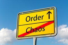 Yellow street sign with Order ahead leaving Chaos behind Stock Photography