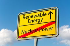 Yellow street sign with renewable energy ahead leaving nuclear p. Ower behind close up Royalty Free Stock Image