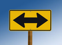 Yellow street sign showing two arrows royalty free stock photo