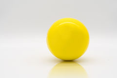 Yellow stress ball rolling on reflection floor. On white background Stock Image