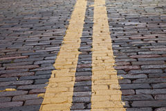 Yellow stripe on brick street Stock Photography