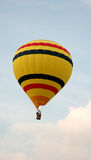 Yellow Striped Balloon. A yellow, striped hot air balloon with the flames shooting up into it takes to the sky Royalty Free Stock Photography
