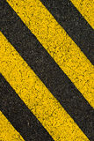 Yellow striped road markings on black asphalt. Royalty Free Stock Photo