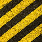 Yellow striped road markings on black asphalt. Stock Photos