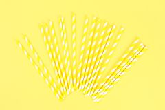Yellow striped straw paper tubes on a bright yellow pastel background. Top view, copy space. Yellow striped straw paper tubes on a bright yellow pastel stock images