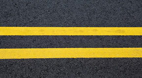 Yellow stripes on asphalt Stock Photography