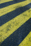 Yellow stripes on asphalt. Background of yellow hatched stripes on asphalt Stock Images