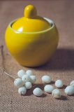 Yellow sugar bowl on a table with white balls Stock Image
