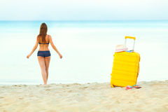Yellow suitcase on the beach and a girl walks into the sea in th Stock Images