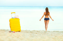Yellow suitcase on the beach and a girl walks into the sea in th Royalty Free Stock Photos