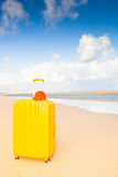 Yellow suitcase at the beach Royalty Free Stock Photos