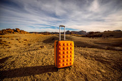 Yellow suitcase on the rocky desert Royalty Free Stock Photos