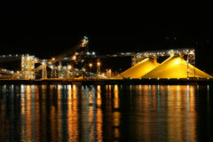 Yellow Sulfur Hill. Large piles of sulfur at shipyard at night time with reflection off water Royalty Free Stock Image
