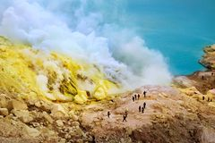 Yellow sulfuric rocks, poisonous smoke and a sulphurous blue lake of crater Ijen Volcano. Caldera of an active volcano. Indonesia. Java island stock photo
