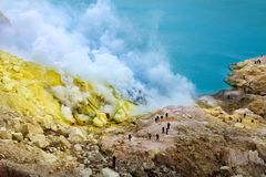Yellow sulfuric rocks and a sulphurous blue lake of crater Ijen Volcano. Caldera of an active volcano. Indonesia. Java island stock photos