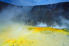 Yellow sulphur on the volcano. And a lot of smoke near the big crater Stock Photography
