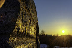 Yellow sun. Sun setting beside a sculpture of granite Royalty Free Stock Images