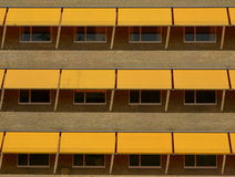 Yellow sun shades. Yellow brick stone building with yellow sun shades over the three window rows stock photography