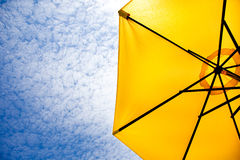 Yellow sun umbrella on a blue sky. Summer background Stock Photography