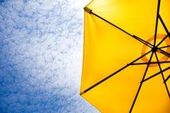 Yellow sun umbrella on a blue sky. Stock Photography
