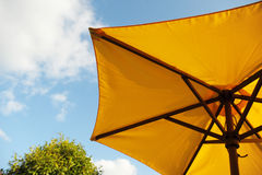 Yellow sun umbrella with sky in background Royalty Free Stock Photos