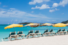 Yellow Sun Umbrellas Over Green Chairs and White Beach Royalty Free Stock Images