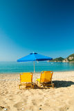 Yellow sunbeds and blue umbrella on a beautiful beach in Corfu I royalty free stock image