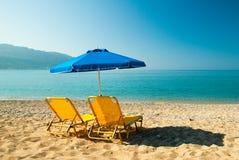 Yellow sunbeds and blue umbrella on a beautiful beach in Corfu I stock image