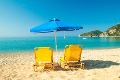 Yellow sunbeds and blue umbrella on a beautiful beach in Corfu I Royalty Free Stock Photo