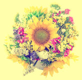 Yellow sunflowers and colored wild flowers in a white vase, close up Royalty Free Stock Images