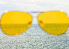 Yellow sunglasses on the sea water and blue sky background. Sunny day, happy vacation, good rest, happiness royalty free stock photo