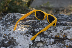 Yellow sunglasses on the stone Stock Images