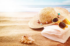 Yellow sunglasses, sunhat and towel on a beach Stock Photography
