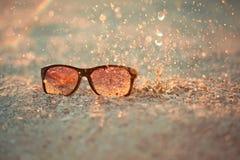 Yellow sunglasseson sandy beach with splash Royalty Free Stock Images