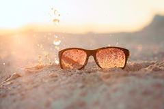 Yellow sunglasseson sandy beach with splash Stock Photos